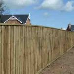 wooden feather edge fence in garden behind house